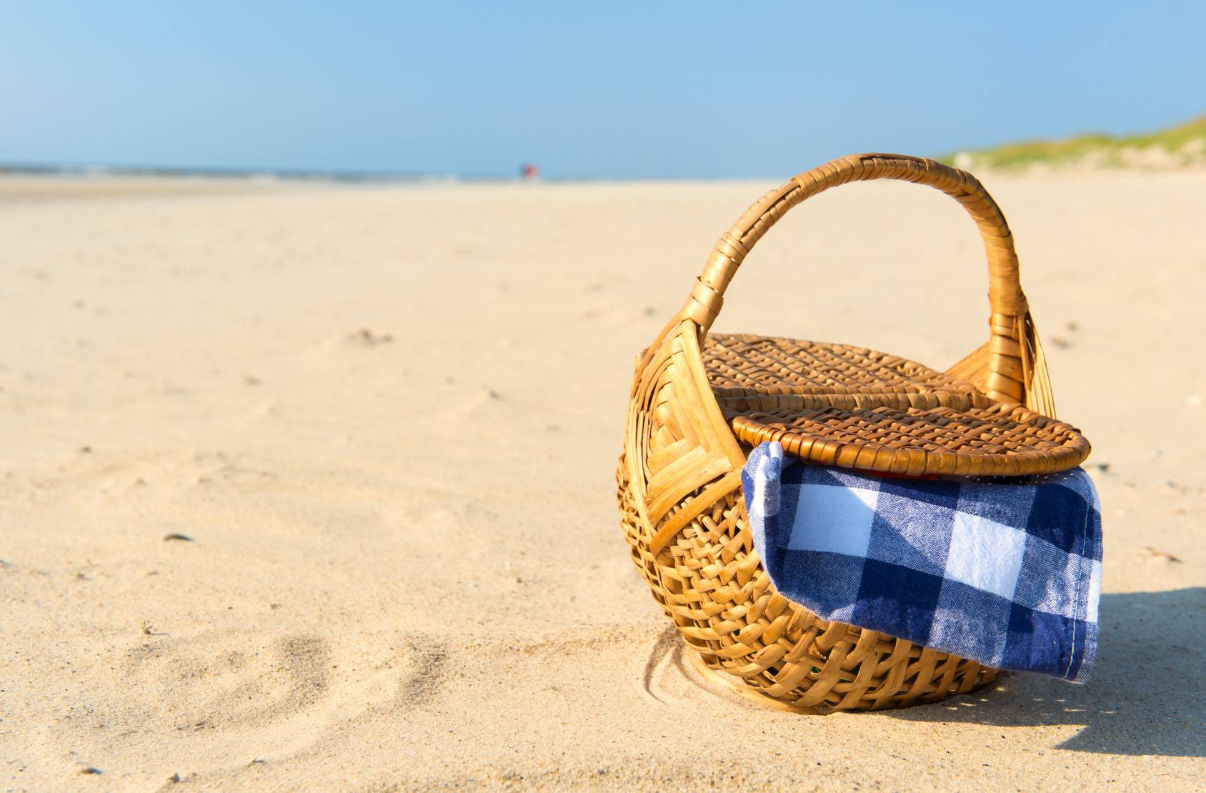 Picnic basket with blue checked cloth at the beach
